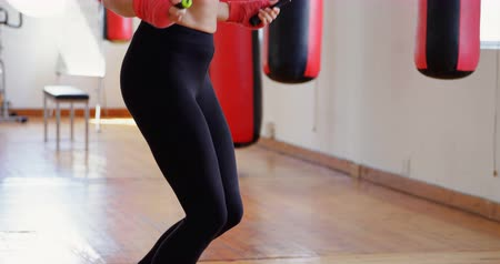 átlyukasztás : Female boxer exercising with skipping rope in fitness studio 4k Stock mozgókép