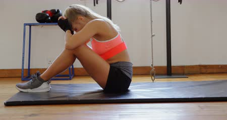 életerő : Side view of female boxer relaxing in fitness studio 4k Stock mozgókép