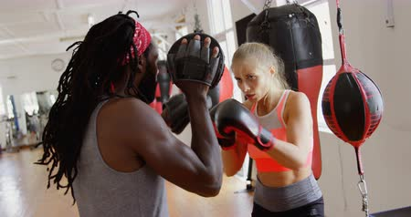 átlyukasztás : Male trainer training female boxer in fitness studio 4k Stock mozgókép