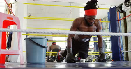 full bucket : Male boxer exercising in boxing ring at fitness studio 4k