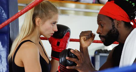 életerő : Male trainer assisting female boxer in fitness studio 4k