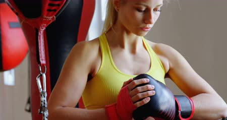 átlyukasztás : Young female boxer standing in fitness studio 4k Stock mozgókép