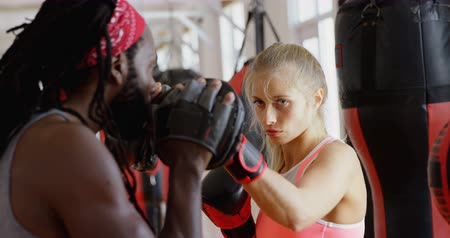 életerő : Male trainer training female boxer in fitness studio 4k Stock mozgókép