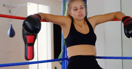 agresja : Female boxer relaxing in boxing ring at fitness studio 4k Wideo