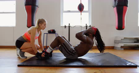 dedicação : Female trainer training male boxer in fitness studio 4k