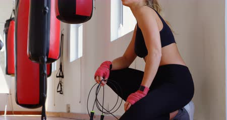 életerő : Young female boxer relaxing in fitness studio 4k