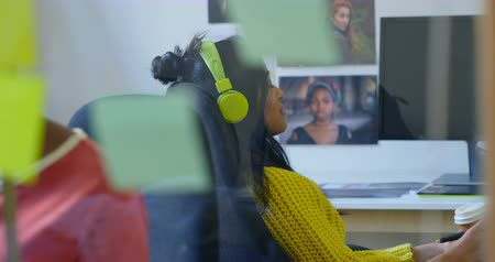 リスニング : Female graphic designer listening music on headphones in office 4k 動画素材