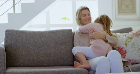 ev gibi : Mother embracing her daughter in living room at home 4k