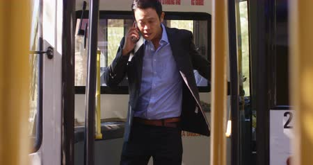 getting : Male business commuter talking on mobile phone while getting out from bus 4k