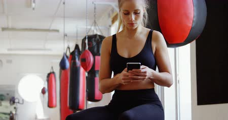 taburete : Young female boxer using mobile phone in fitness studio 4k