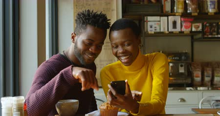 kafeterya : Front view of sweet young couple enjoying themselves, while using mobile phone in cafe in slow motion Stok Video