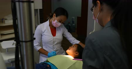 surgical mask : Side view of attentive female Asian dentist wearing white lab coat interacting with young patient in clinic at an appointment