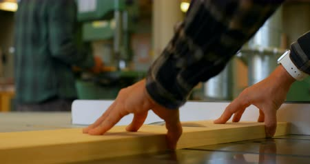 zagen : Close-up of a carpenters hands making a precise cut using table saw in workshop , with his coworker blurry in the background Stockvideo
