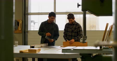 velo : Male carpenter using table saw to cut wood working in workshop, with his coworker holding a digital tablet and giving instructions