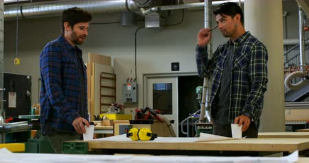earmuffs : Front view of young carpenters interacting with each other while drinking coffee in workshop