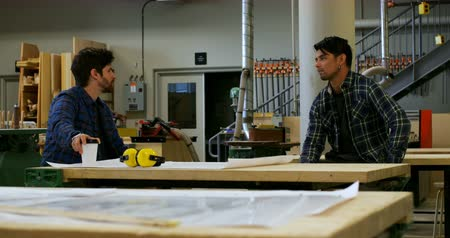 earmuffs : Front view of young carpenters sitting down and interacting with each other in workshop while having coffee Stock Footage