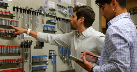machinist : Side view of well dressed male engineers using digital tablet to check spare tools, displayed on wall in workshop