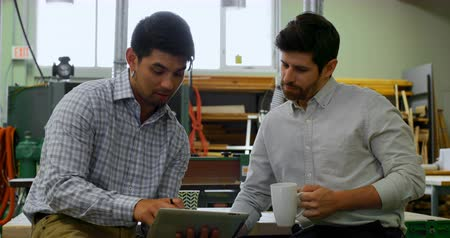 work station : Front view of well dressed young male engineers interacting with each other in workshop, while having coffee Stock Footage