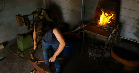 hot rod : High angle view of a female metalsmith molding glowing hot horseshoe in factory. She hits with a hammer and a chisel with fire in the background.