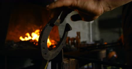 heating up metal : Close-up of female metalsmith heating horseshoe in fire, operating a horseshoe shaped lever.