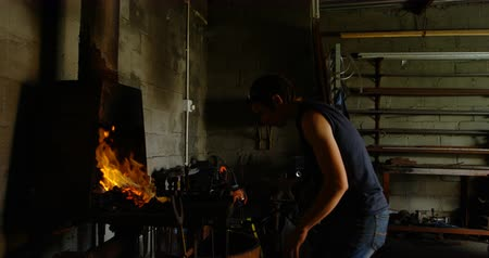 metal işi : Side view of young female metalsmith with short hair heating horseshoe in fire at factory.