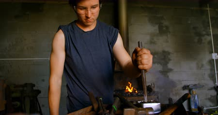 внимательный : Front view of young female metalsmith with short hair working in workshop. Fire in the background.