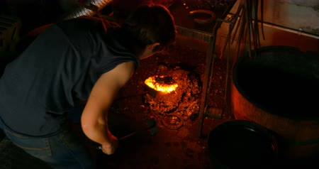 подкова : Rear view of young female with short hair metalsmith heating horseshoe in fire at factory.