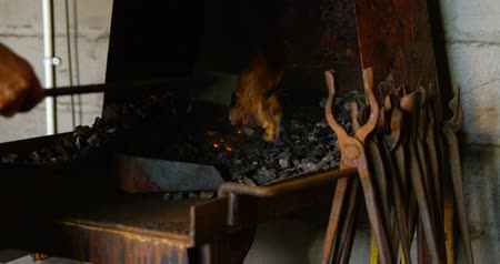 at nalı : Close up of female metalsmith hands and tool heating horseshoe in fire at factory