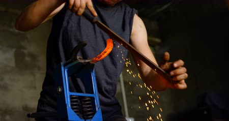 metal işi : Front view of an attentive focused young female metalsmith shaping glowing hot horseshoe in factory. Stok Video