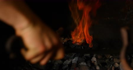 heating up metal : Close-up of metalsmith hand and tools heating horseshoe in fire.