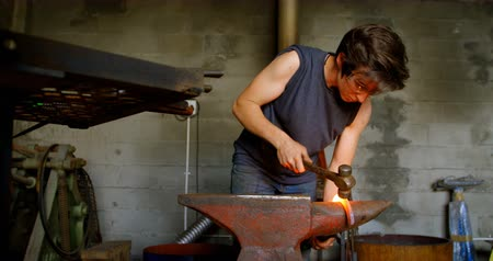 hot rod : Attentive female metalsmith molding a glowing hot horseshoe in factory, hitting it with a hammer. Stock Footage