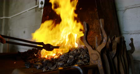 heating up metal : Close-up of metalsmith hands and tools heating horseshoe in fire. Stock Footage