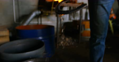 hoefijzer : Close-up of a young female metalsmith removing horseshoe from water. Fire in the background. Stockvideo
