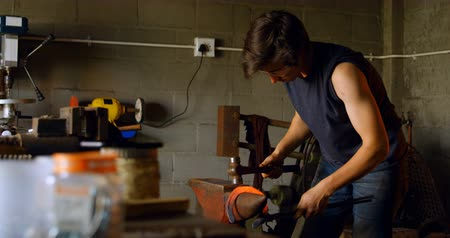 hot rod : Attentive and focused young female metalsmith with short hair molding glowing hot horseshoe in factory.