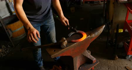 hot rod : High angle view of mid section of young female metalsmith holding hot horseshoe in factory. Stock Footage