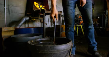 подкова : Low section of metalsmith working in workshop. The young women is cooling a horseshoe. Стоковые видеозаписи