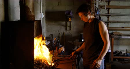 подкова : Side view of a young female metalsmith with short hair heating horseshoe in fire at factory.