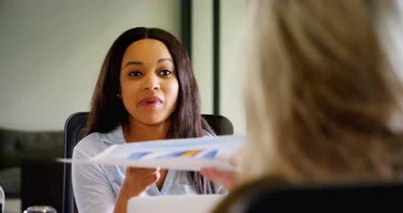 holding document : Over the shoulder view of smiling happy mixed race and multi-ethnic business colleagues interacting with each other at desk in office.
