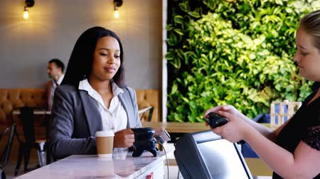 job transfer : Front view of a young pretty mixed race businesswoman making payment through NFC in a cafe 4k. The well dressed female pay with credit card. Stock Footage