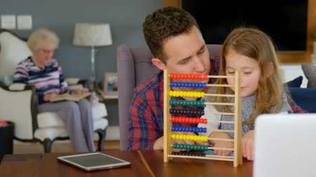 abacus : Father and daughter playing with abacus in living room at home while grand mother is reading in the background. Family having fun and spending time together. Stock Footage