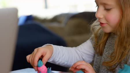 ev gibi : Close up of a cute little girl playing with modeling clay in living room at home. Daughter having fun while playing on the table.