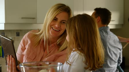 prepare food : Close up of a lovely mother and cute daughter using digital tablet and having fun while preparing food in the kitchen at home. Father and Daughter are looking for recipe in the background. Stock Footage
