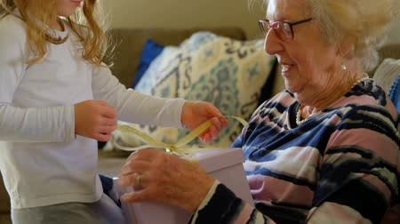 homely : Side view lovely granddaughter giving gift to her grandmother in living room at home. They undo the yellow ribbon to unbox the gift. Stock Footage