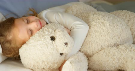 ev gibi : Girl sleeping with teddy bear in bedroom at home. Hugging teddy bear and smiling 4k Stok Video