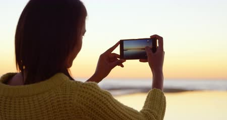 klick : Rear view of beautiful woman capturing sunset on mobile phone. View of calm sea and dramtic sky in the background 4k