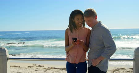 korkuluk : Couple using mobile phone near beach. Sea waves in the background 4k Stok Video