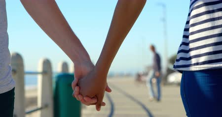 mid section : Close-up of couple walking hand in hand on the promenade. Mid section of couples hand against the blue sky 4k Stock Footage