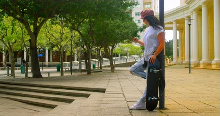 accoudé : Young woman using mobile phone while leaning on pole with skateboard. City in the background 4k Vidéos Libres De Droits