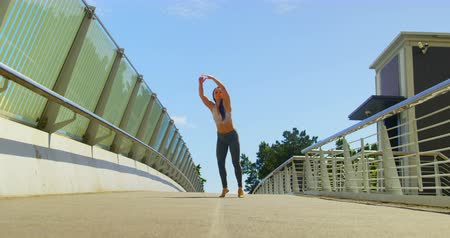 balanceamento : Young female dancer dancing on a bridge in the city. Blue sky in the background 4k