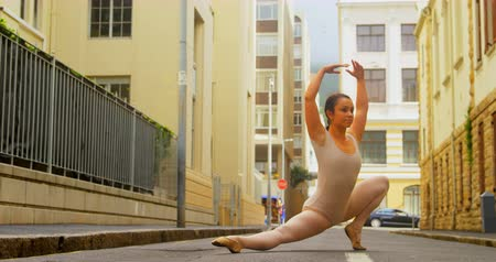 kiegyensúlyozó : Young ballerina practicing ballet dance on the street in the city. Buildngs in the background 4k